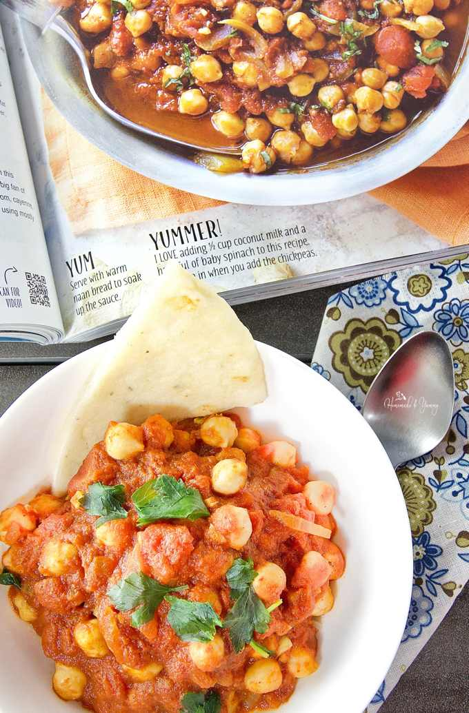 Overhead shot of chana masala in a bowl with a picture of the cookbook in the background.