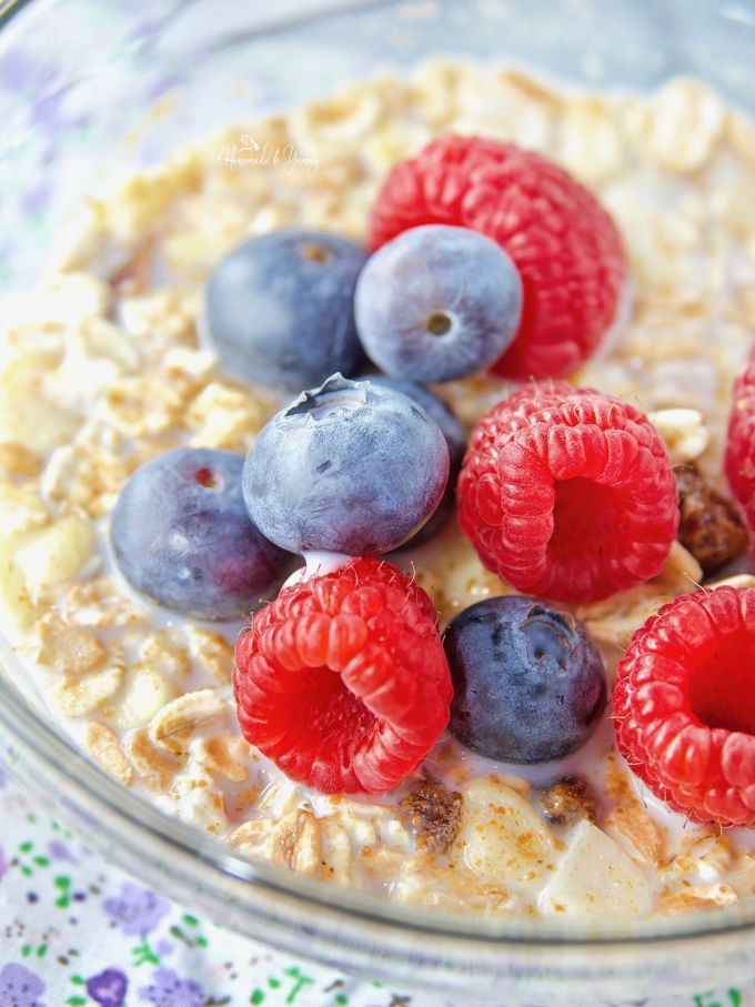 Muesli cereal in a bowl with fresh raspberries, blueberries and milk.