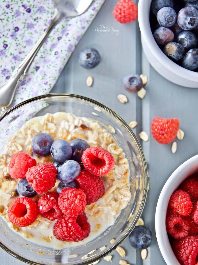 Easy muesli in a serving bowl with fresh raspberries, blueberries and milk.
