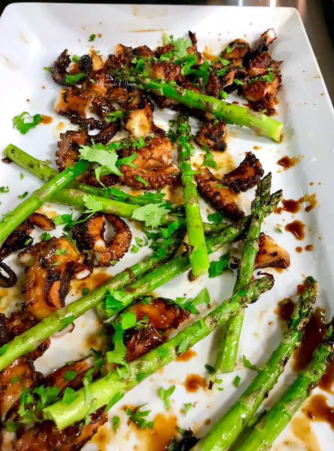 Grilling Seafood and some grilled octopus and asparagus on a platter.
