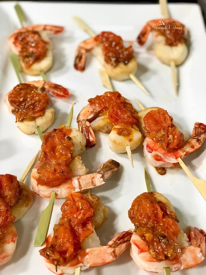 Grilling Seafood namely shrimp on skewers with a tomato sauce.