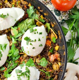 Poached Eggs & Lentil Hash in a pan sprinkled with fresh parley, ready to serve.