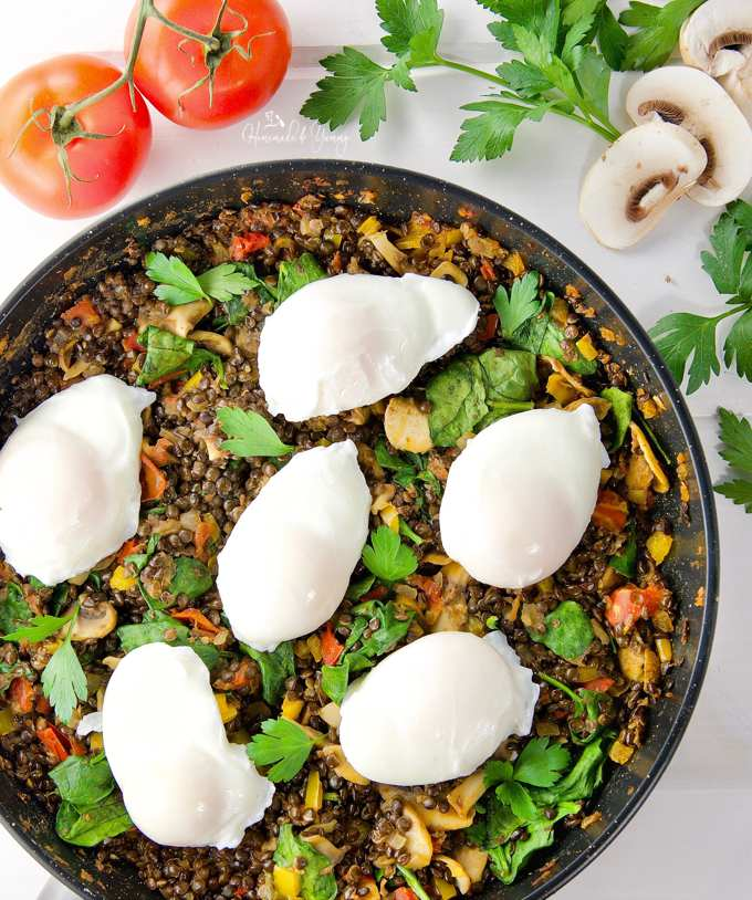 Poached Eggs & Lentil Hash in a pan ready to garnish and serve.