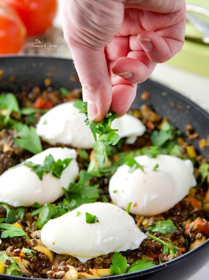 Poached Eggs & Lentil Hash getting garnished with fresh parsley before serving.