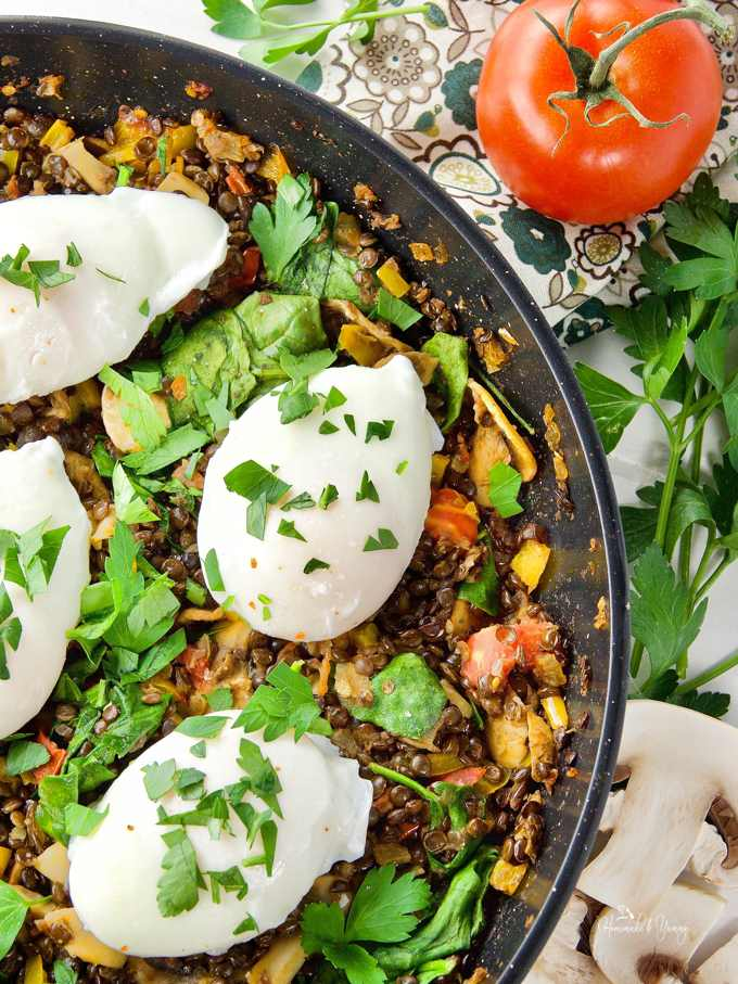 Poached Eggs & Lentil Hash in a pan garnished with fresh parsley ready to serve.