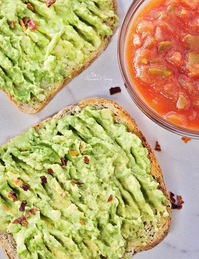 Mashed avocado getting spread on toast.
