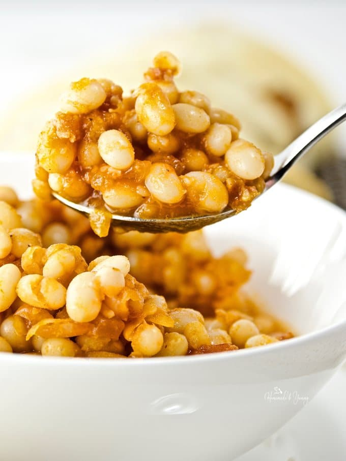 Close up shot of baked beans on a spoon.