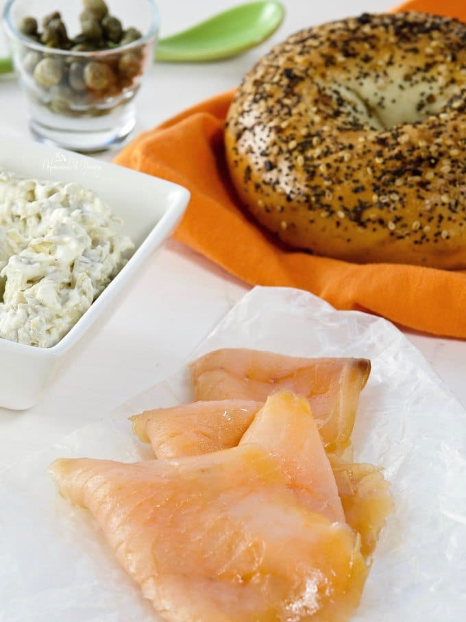 Recipe ingredients, smoked salmon, bagel, cream cheese and capers.