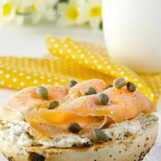Closeup of Smoked Salmon Bagel with Artichoke Cream Cheese, cup of coffee in the background.