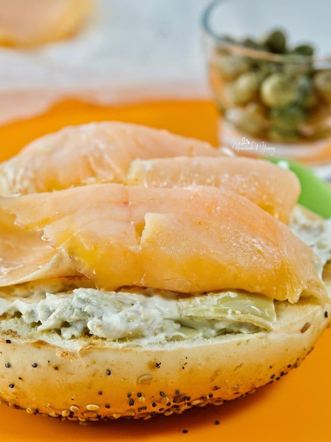 Closeup of slices of smoked salmon piled on cream cheese on a toasted bagel.