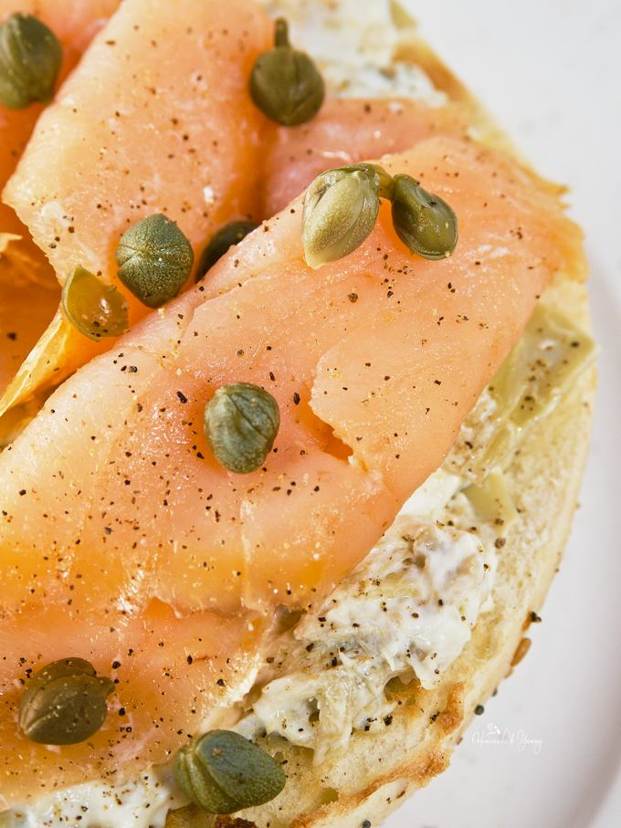 Close up of toasted bagel topped with cream cheese, slices of smoked salmon, garnished with capers and freshly ground black pepper.