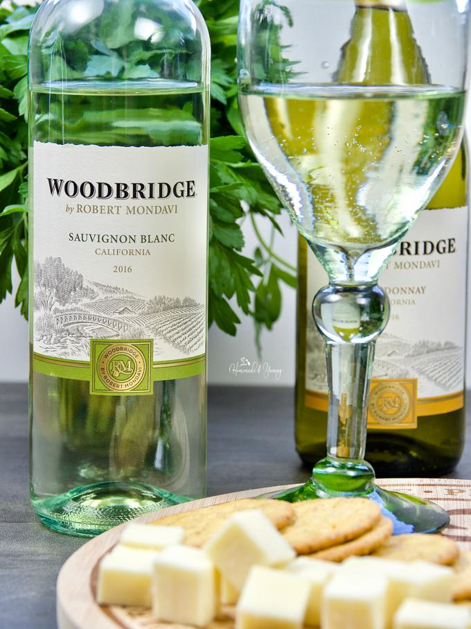 A bottle of Woodbridge by Robert Mondavi wine and board of cheese and crackers.