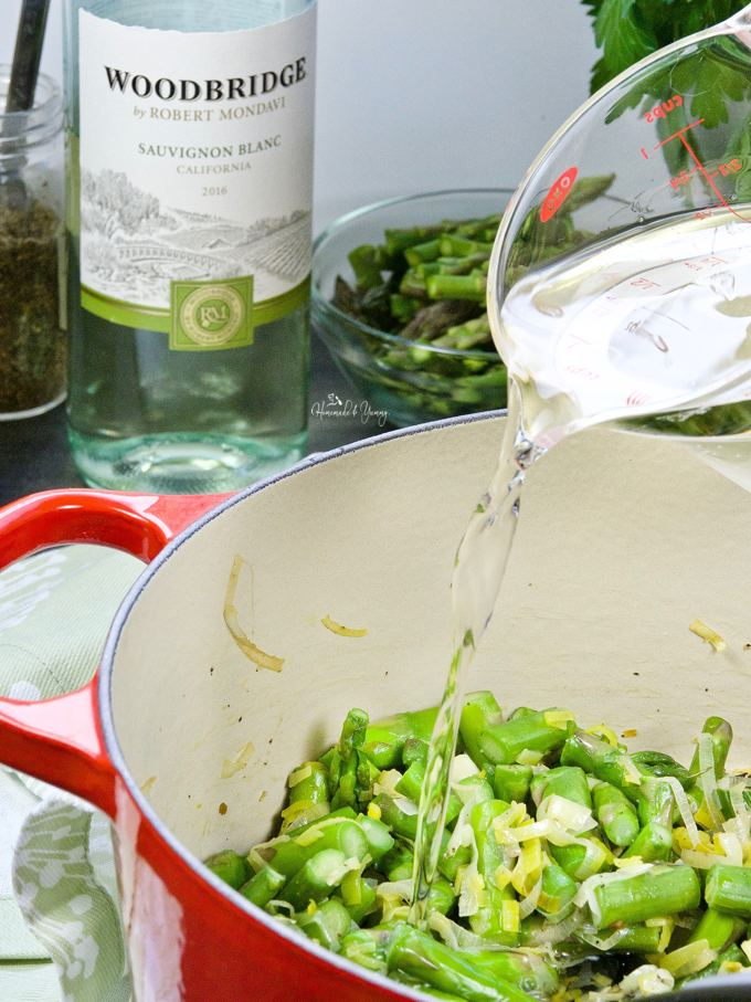 Wine getting poured into the pot of asparagus cooking for the soup.