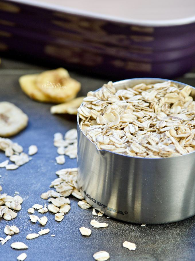 Oatmeal in a measuring cup, banana chips and baking dish in the background.