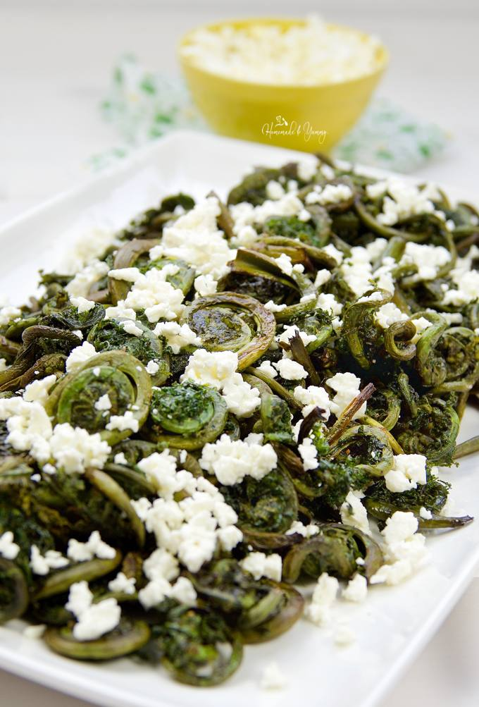 Fiddleheads on a serving plate, garnished with feta cheese ready to eat.