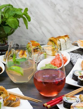 Wine Spritzers on a table with plates of sushi.