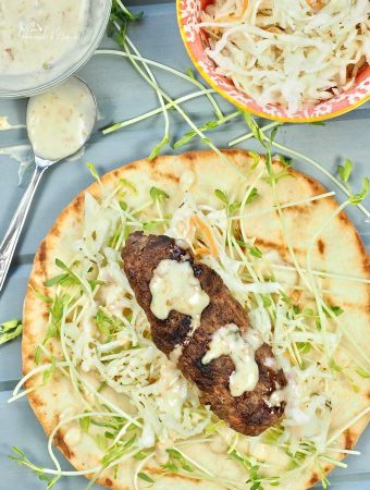 Grilled Kofta Kebabs Made with LAMB on naan bread, garnished and ready to eat.