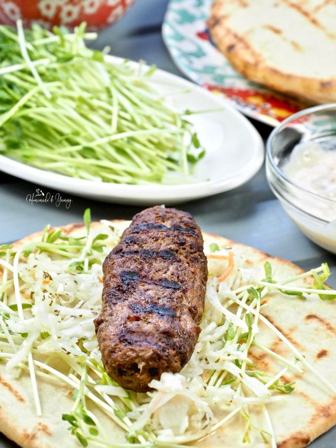 Close up of grilled lamb kofta on naan bread waiting to get garnished.