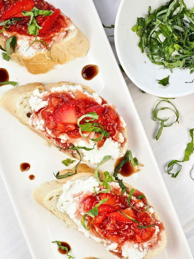 Slices of bread topped with Sweet Strawberry Bruschetta on a serving platter.