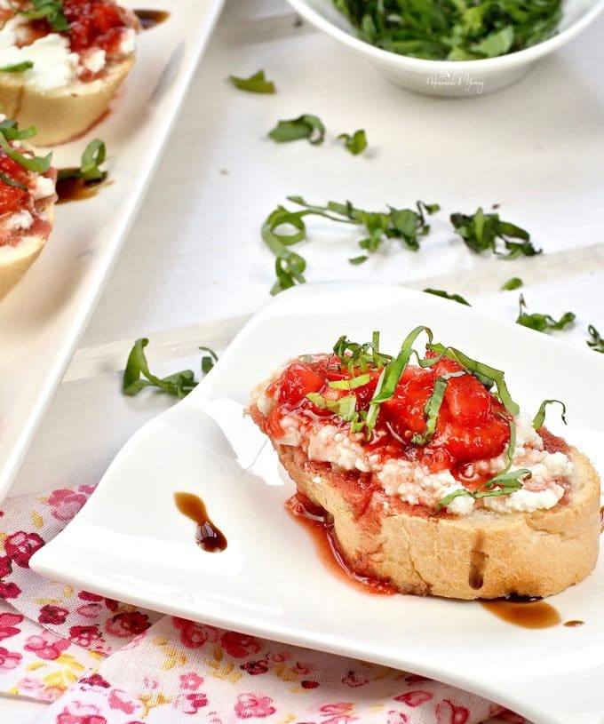 Close up of a slice of bread with ricotta and strawberry bruschetta topped with thin stands of fresh basil.