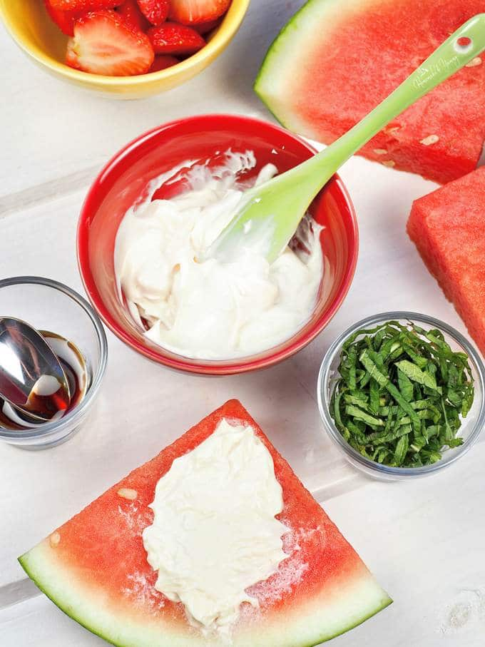 Watermelon slices getting topped with fruit pizza ingredients.