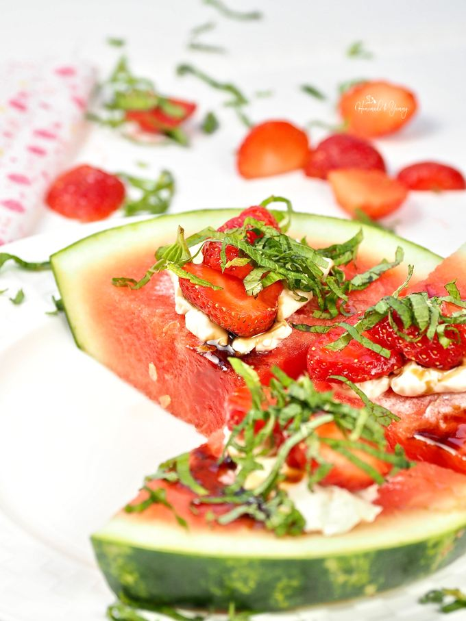Slices of Watermelon Fruit Pizza on a serving plate.