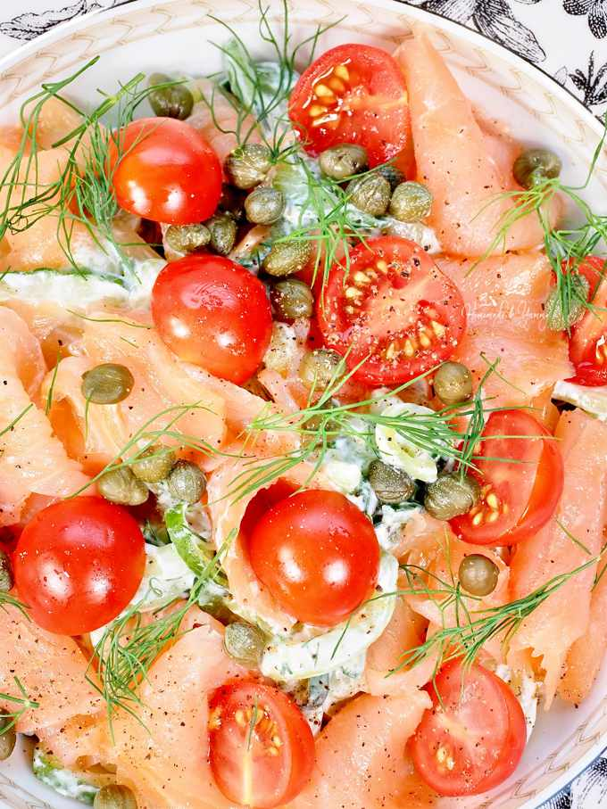 Closeup shot of smoked salmon salad garnished with dill, capers and tomatoes.