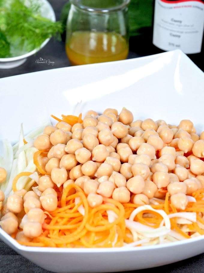 Chickpeas in a bowl with carrots and fennel ready to get mixed into a salad.