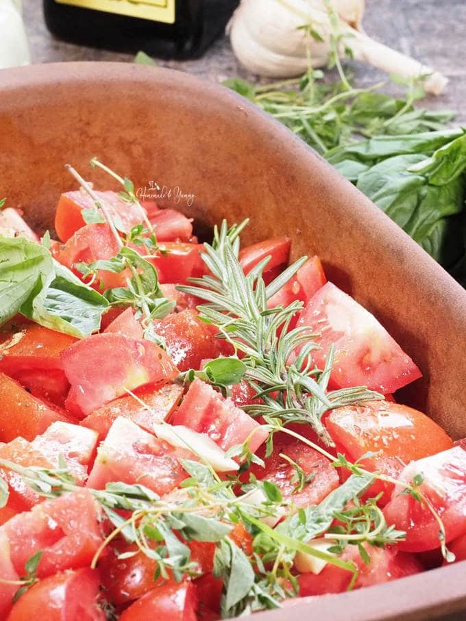 Tomatoes cut up in a baking dish, with oil, spices and herbs.