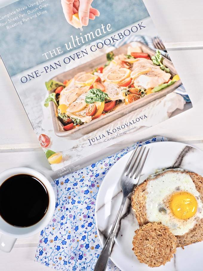 Overhead shot of the cookbook (for giveaway) and a Smoked Salmon Egg In A Hole on a plate with a cup of coffee.
