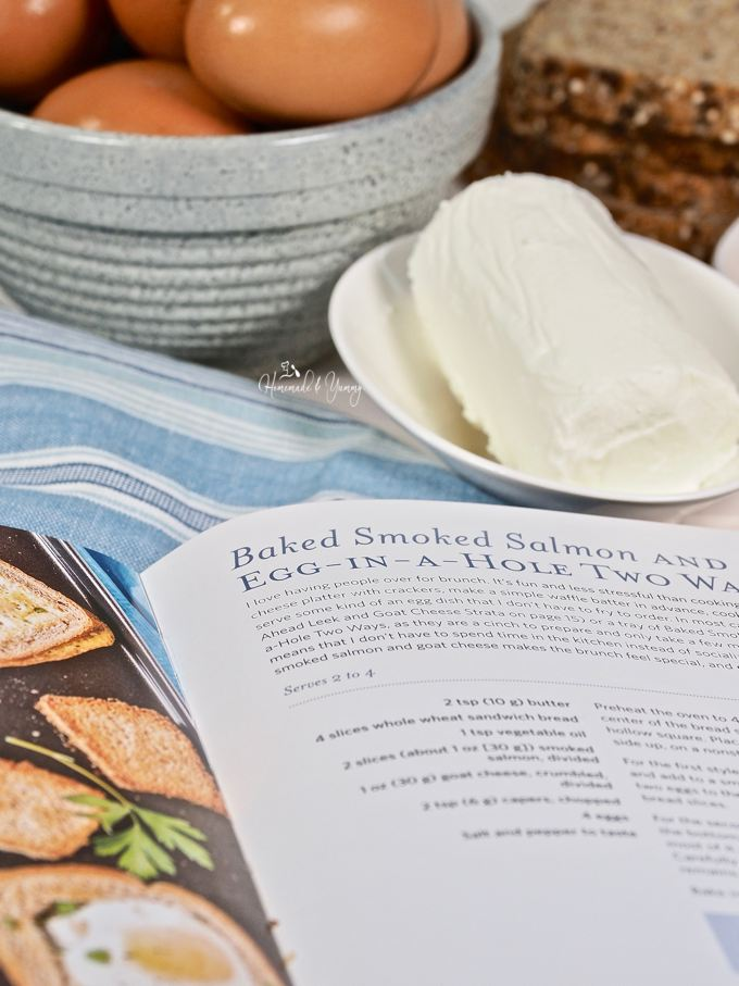 Cookbook opened to the Smoked Salmon Egg In A Hole recipe page.