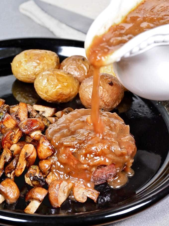 Onion Gravy with Red Wine getting poured onto a steak.