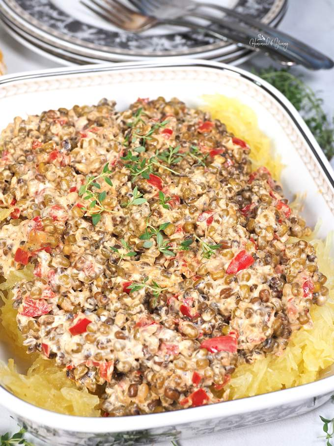 Puy Lentil Pasta Sauce on top of spaghetti squash in a casserole dish.