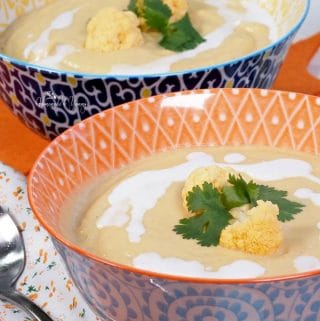 Close up of Roasted Orange Cauliflower Blender Soup with Curry in a bowl garnished with coconut milk and raw cauliflower florets.