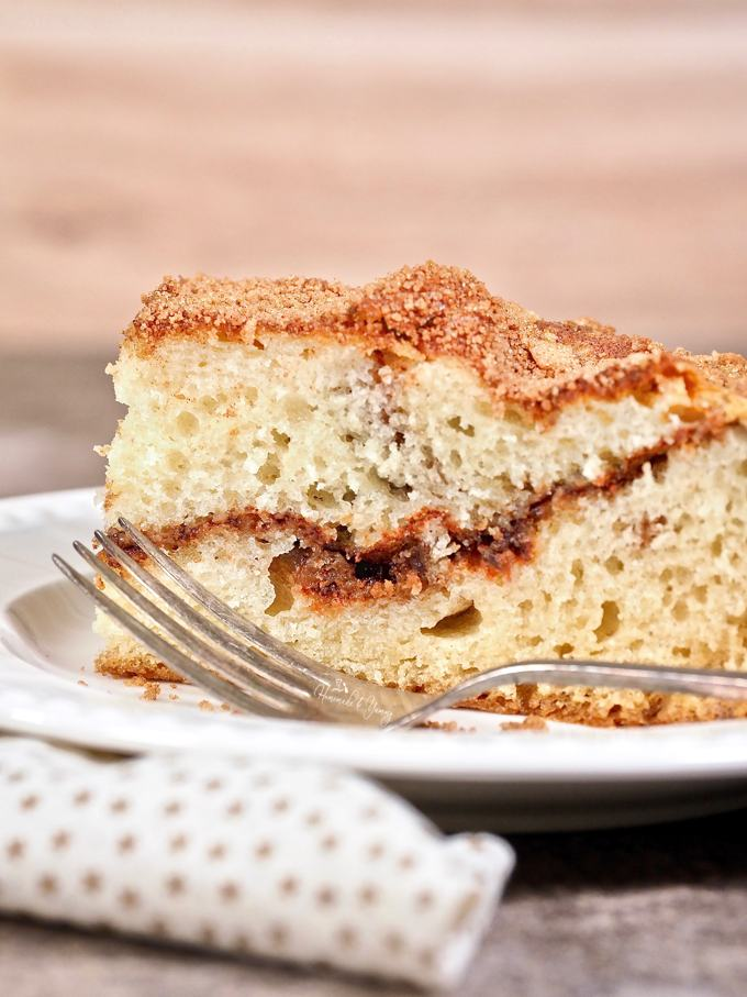 Simply Cinnamon Coffee Cake on a plate with a fork ready to eat.
