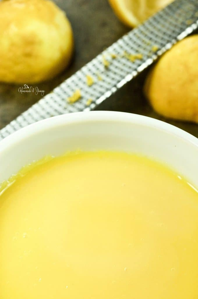 Lemon curd cooked and cooling in a bowl.