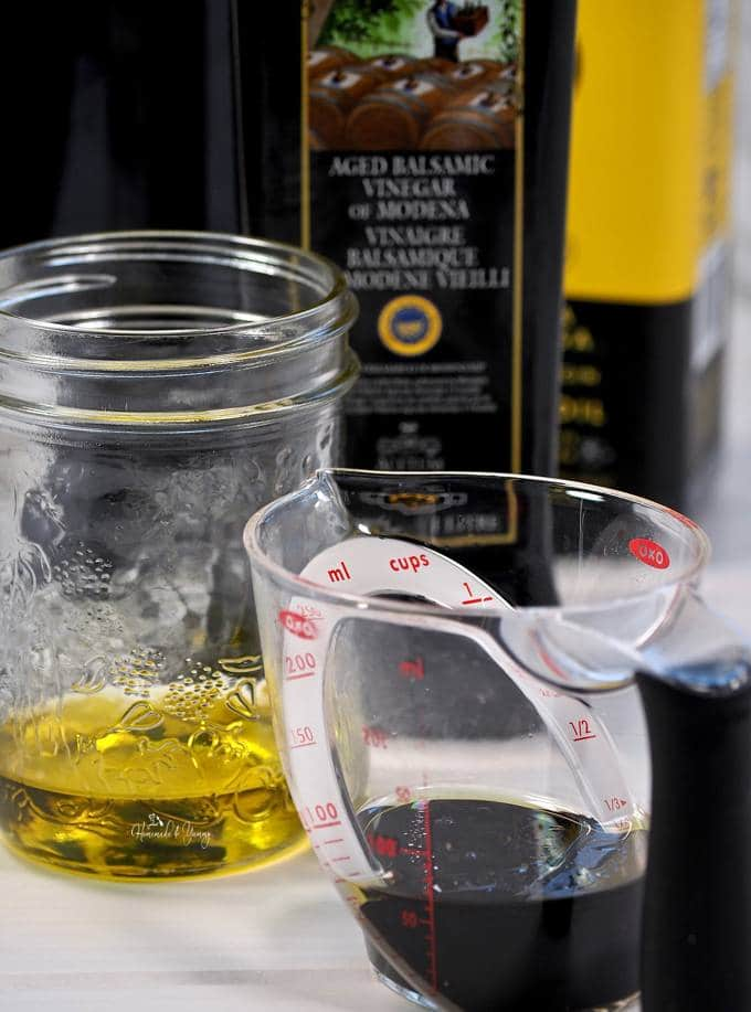 Olive oil in a jar, balsamic vinegar in a measuring cup.