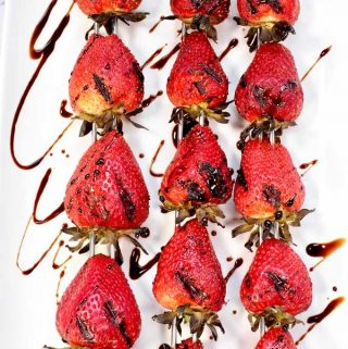Grilled Balsamic Strawberries on a plate drizzled with glaze ready to eat.