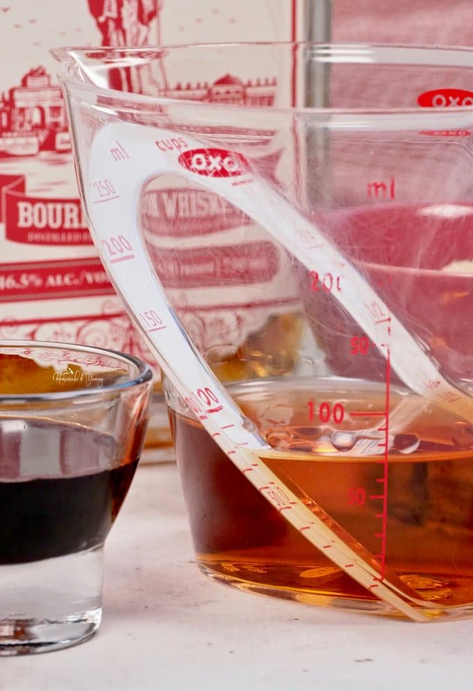 A measuring cup with bourbon in it.