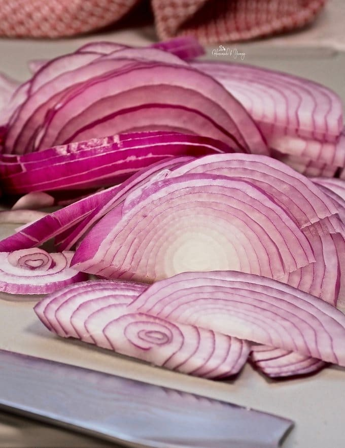 A pile of thinly sliced red onions.