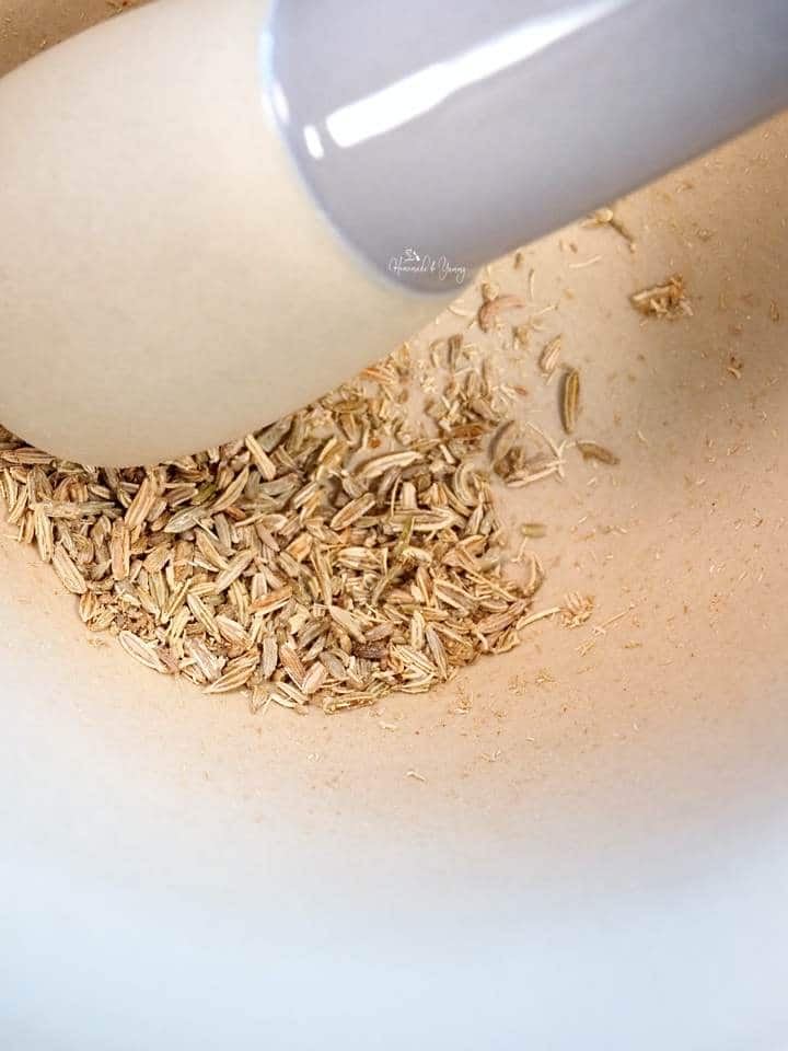 Fennel seeds getting crushed in a mortar and pestle.
