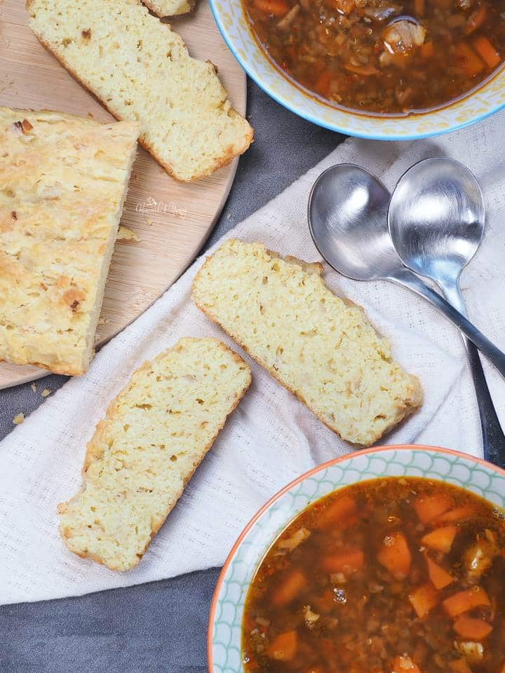 Slices of bread along side bowls of soup.