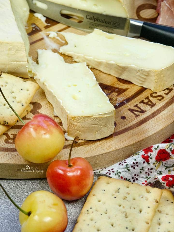 Slices of smoked brie cheese on a wooden board.