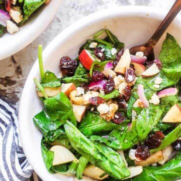 Apple spinach salad in a serving bowl.