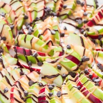 A plate of sliced apples drizzled with peanut butter and chocolate chips.