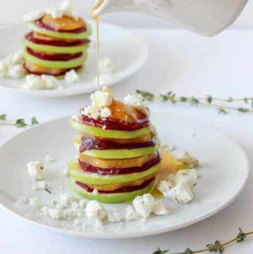 Salad of sliced apples and beets stacked on a plate.