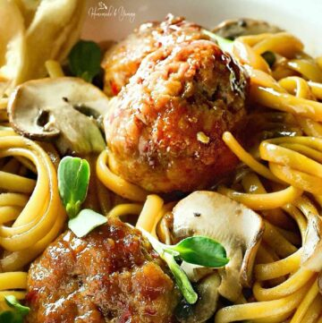 Close up of spaghetti and meatballs Chinese style with pea shoots and mushrooms.
