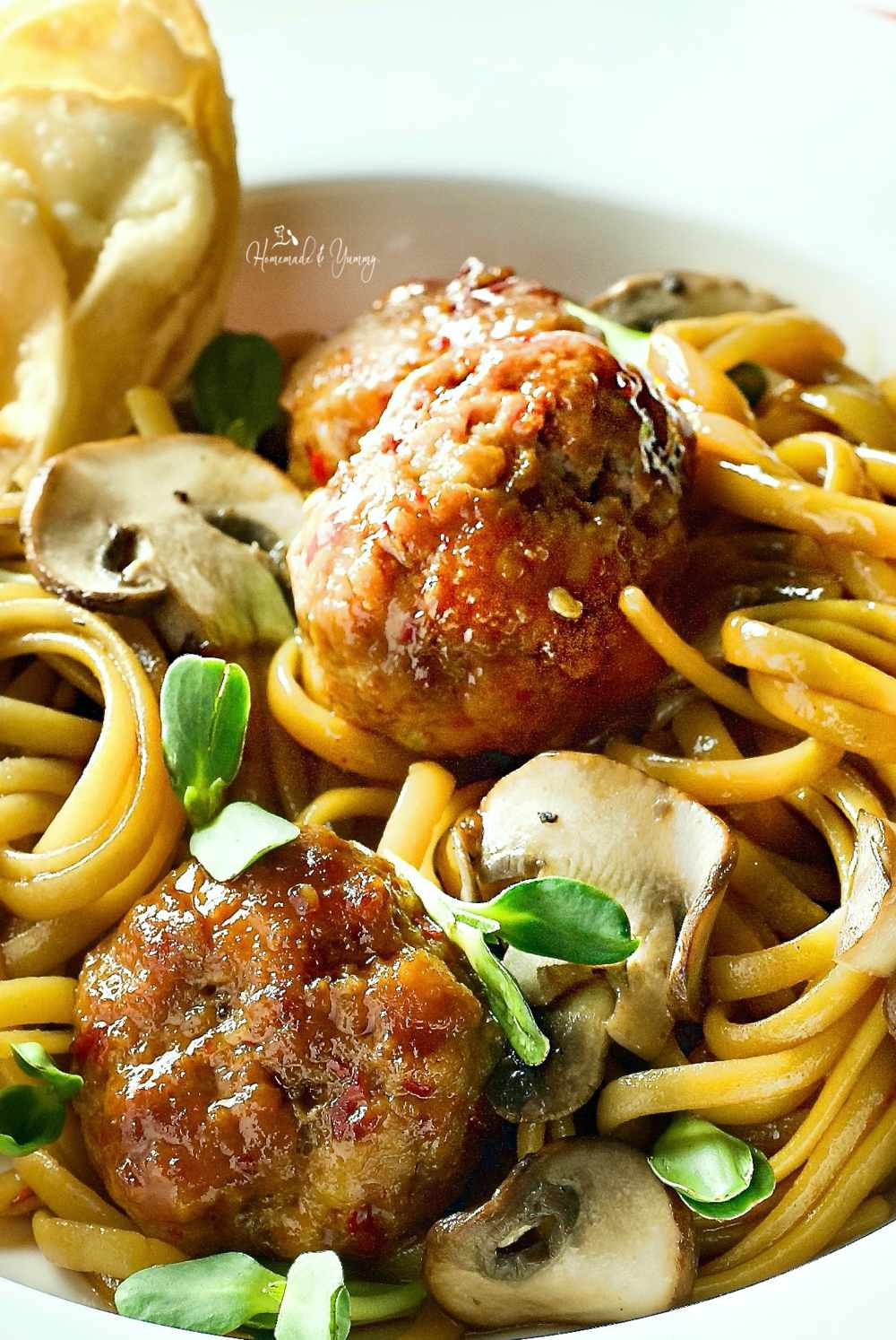 Spaghetti and meatballs Chinese style with pea shoots and mushrooms.