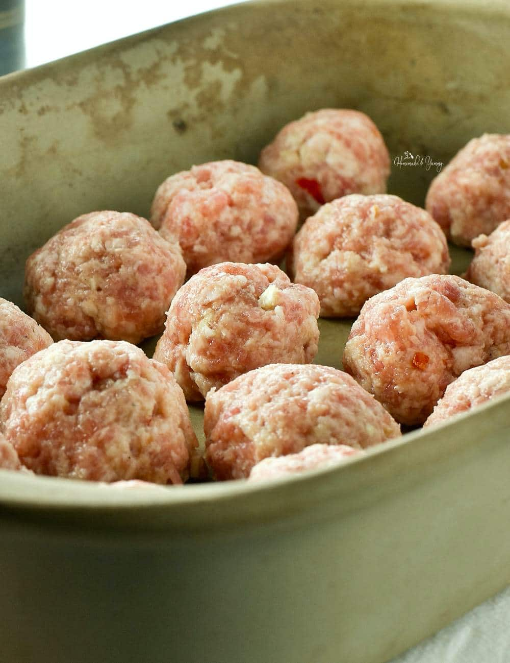 Pork meatballs in a baking dish ready to go into the oven.