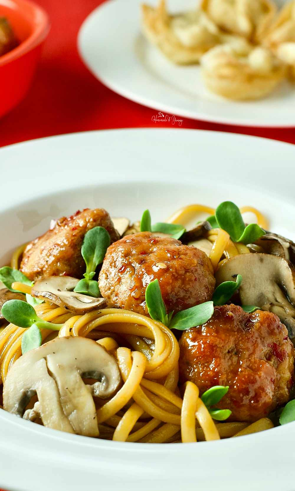 Asian spaghetti with pork meatballs in a bowl.